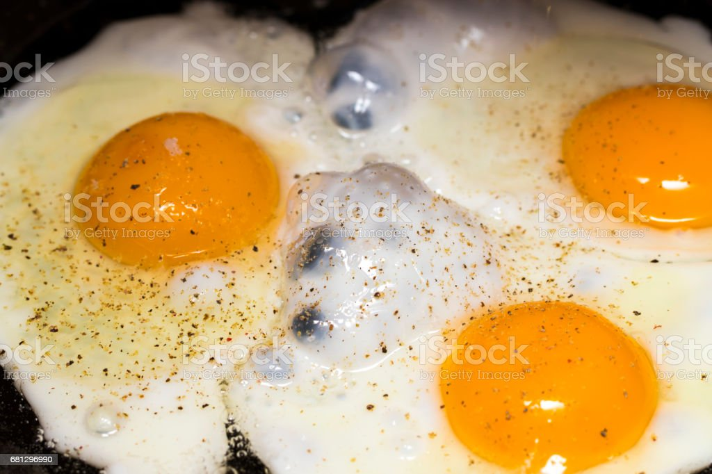 Fried eggs in a frying pan  for breakfast on a black background stock photo