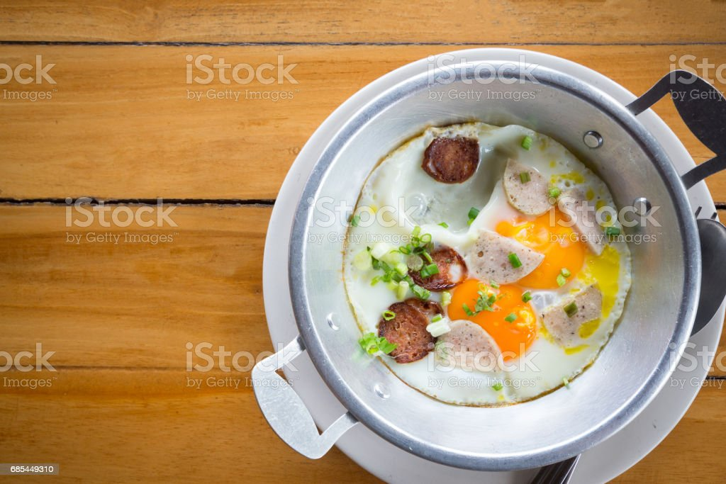 Fried eggs in a frying pan with sausage with pork mixed black pepper ,Breakfast, Healthy food. stock photo
