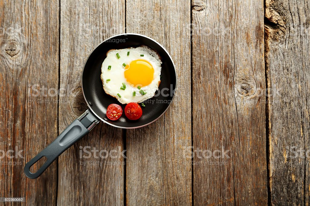 Fried eggs in pan on grey wooden table stock photo