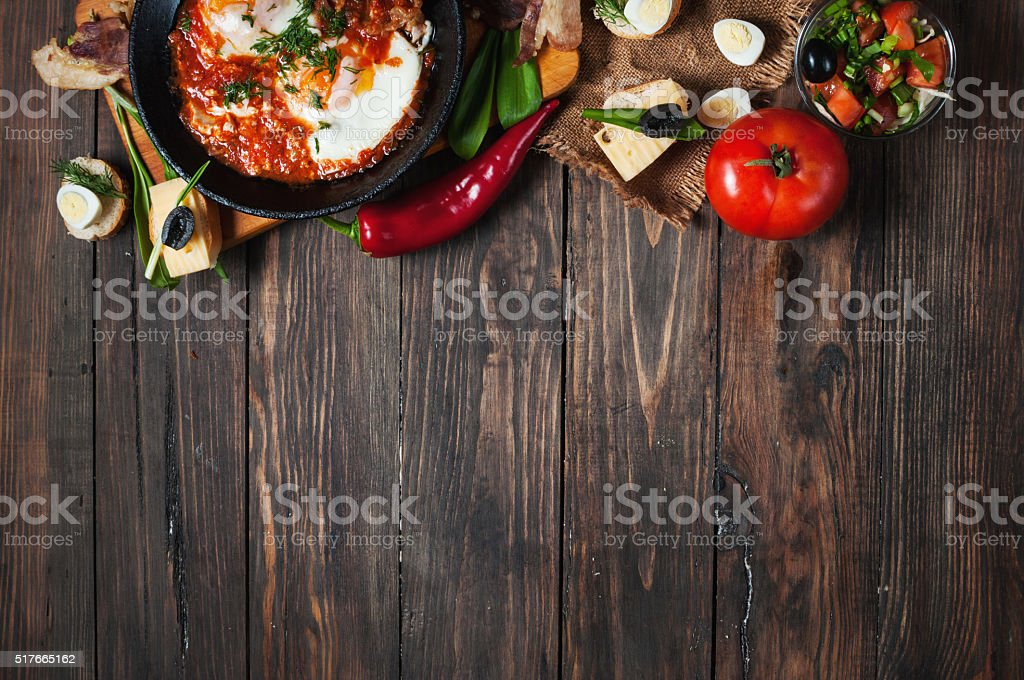 fried eggs with bacon in a pan close-up stock photo