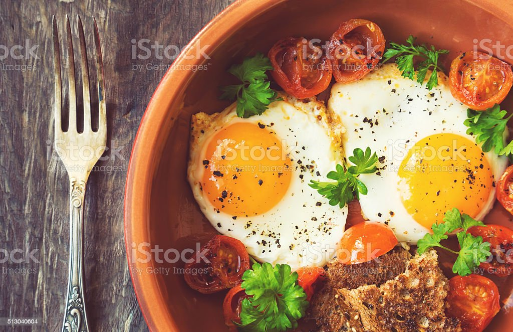 Fried eggs with cherry tomatoes and parsley in clay dish stock photo