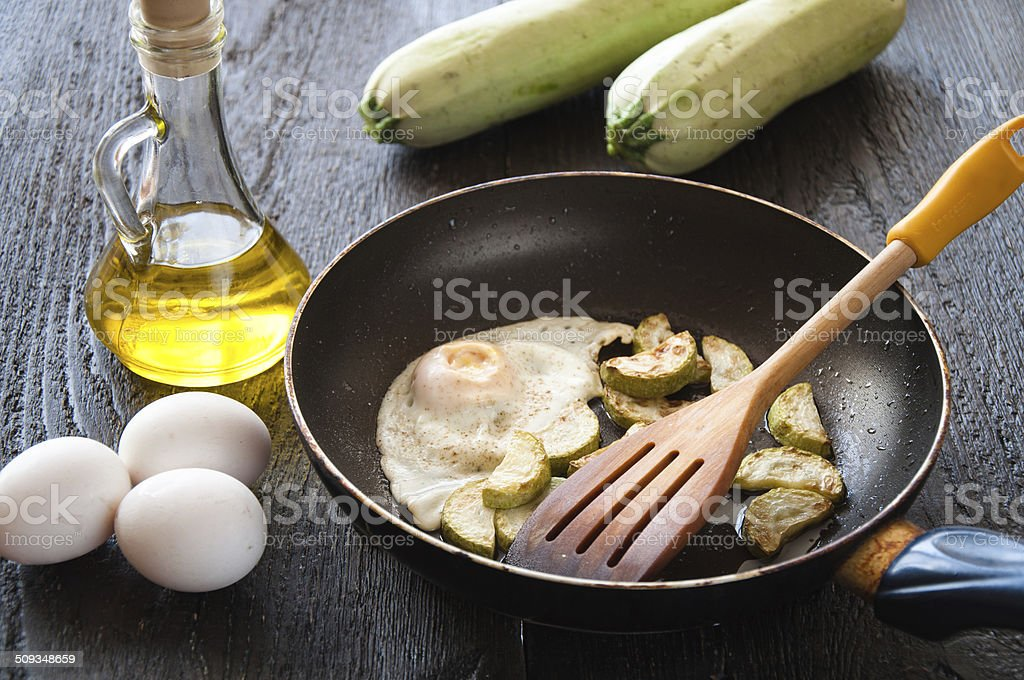fried eggs with zucchini and parsley stock photo