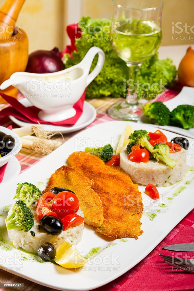 Fried Fish Boilde Rice and Broccoli Cherry Tomatoes and Olives stock photo