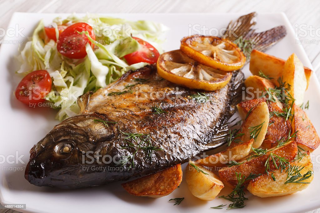 fried fish carp with potato and salad on a plate stock photo
