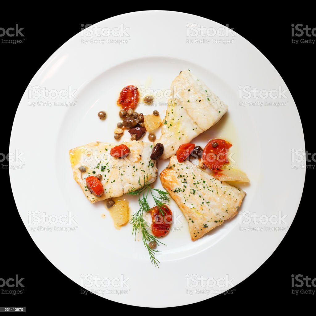 Fried fish fillet with capers isolated on black stock photo