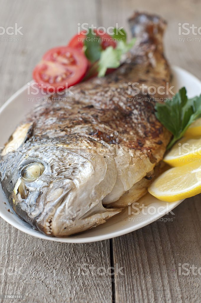 Fried (roasted) Fish (Dorado) Garnished with Lemon, Tomato royalty-free stock photo