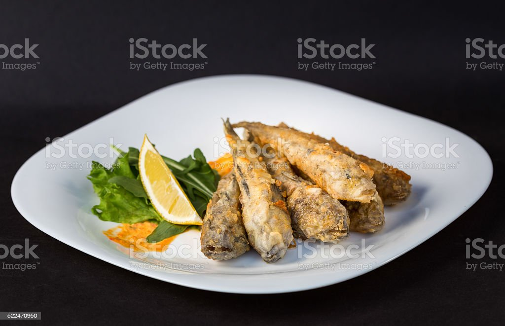 Fried fish gobies in batter with lemon and greens stock photo