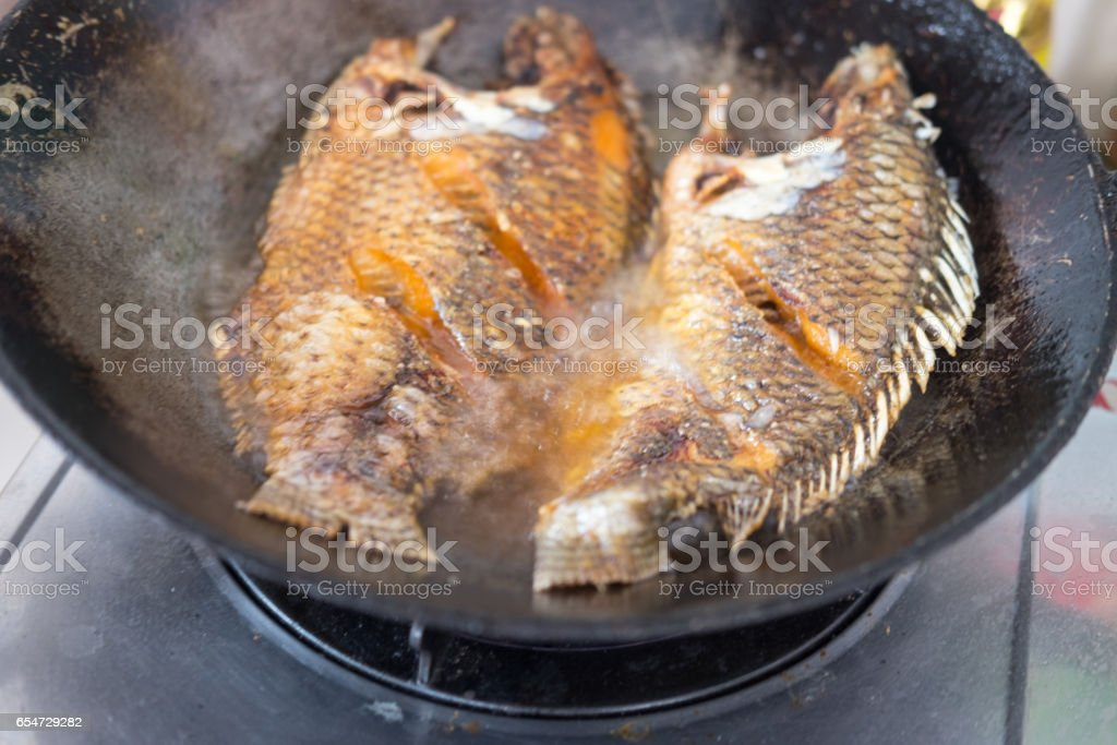 Fried fish in a frying pan in the kitchen stock photo