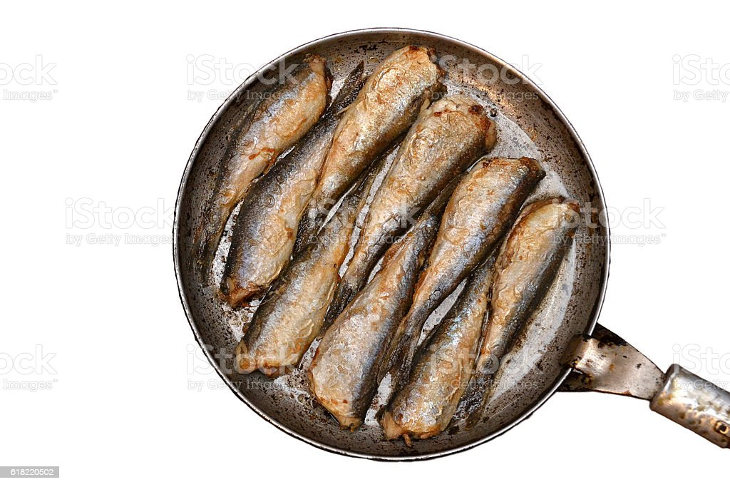 Fried fish in a frying pan, isolated stock photo