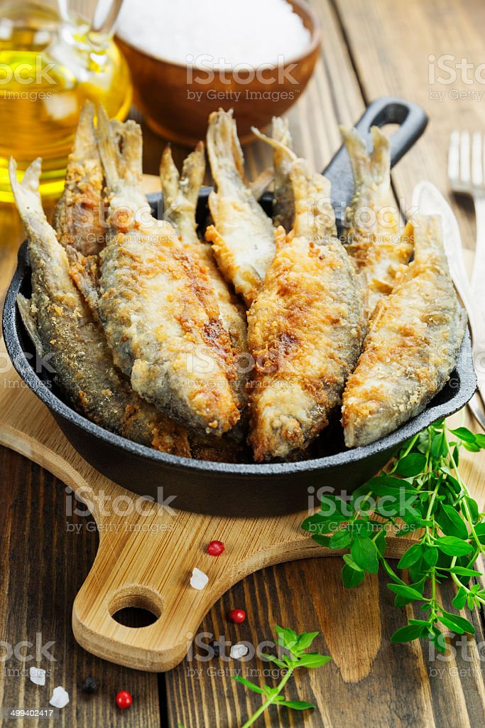 Fried fish in a frying pan royalty-free stock photo