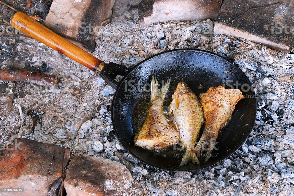 Fried fish on the fire in a skillet. stock photo