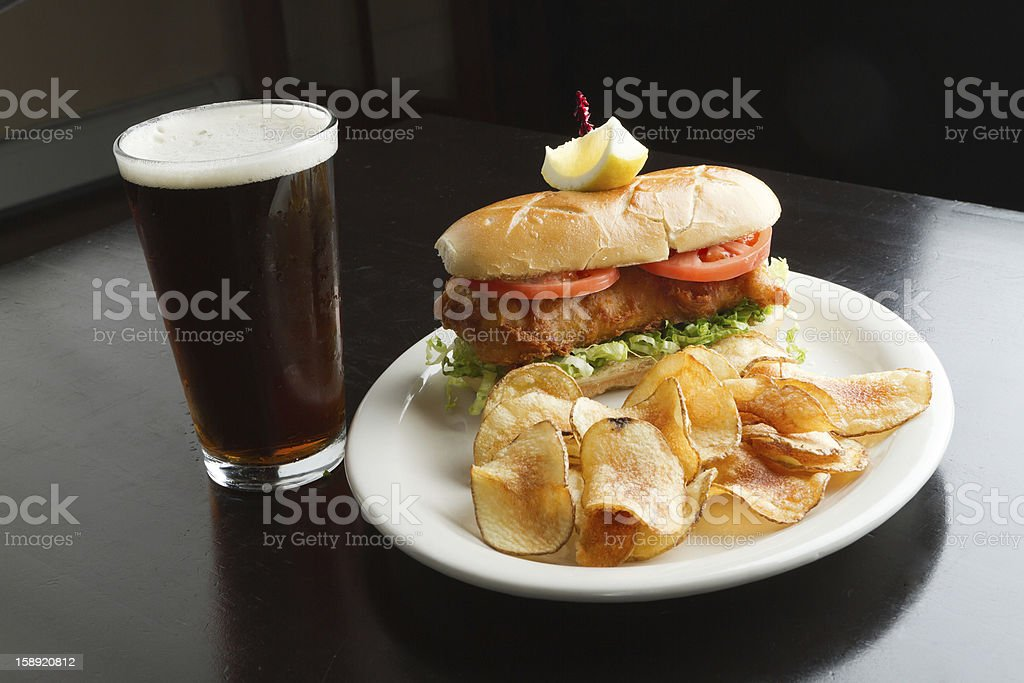 Fried Fish Sandwich and Chips with Beer royalty-free stock photo