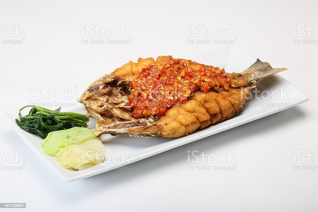 Fried fish topped with chili sauce stock photo
