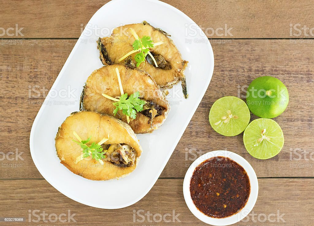 Fried fish with chili sauce on a white plate. stock photo