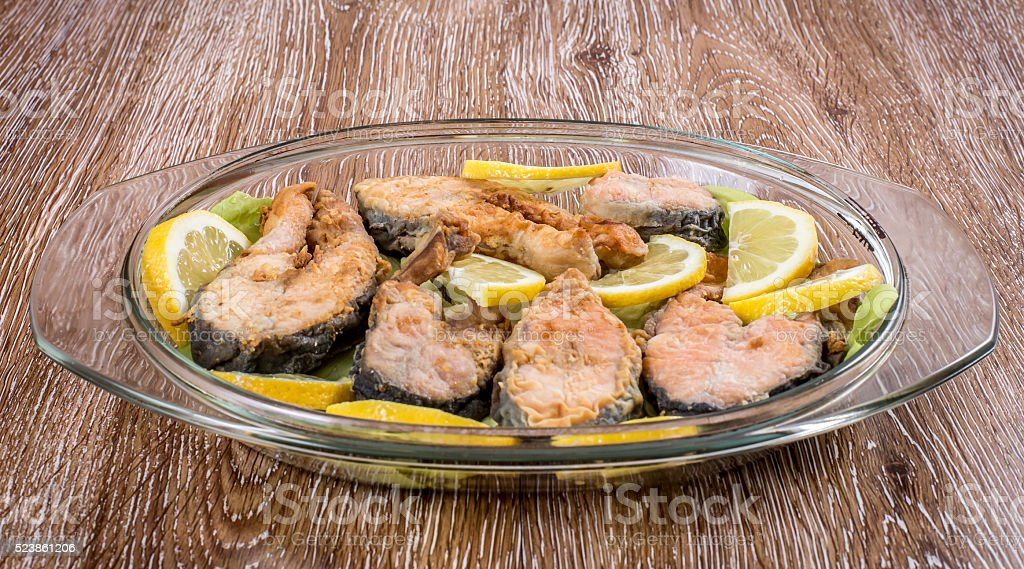 Fried fish with sliced lemon in a plate stock photo