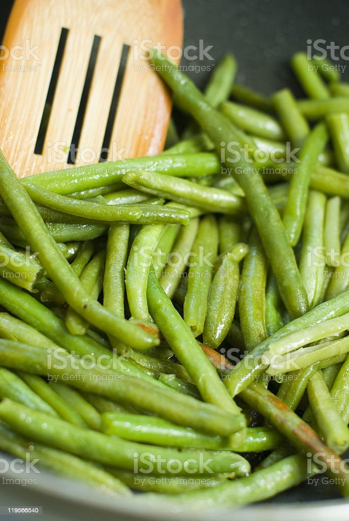 Fried green beans and wood utensils stock photo