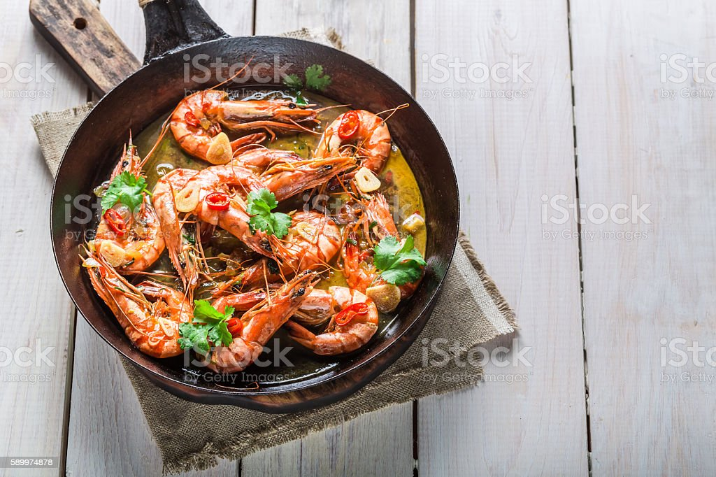 Fried king prawns served on hot pan stock photo