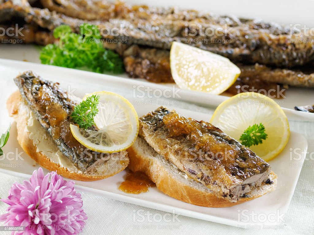 Fried lamprey canapes on a baguette with lemon royalty-free stock photo