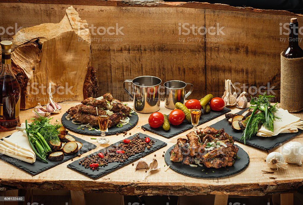 Fried meat, marinated vegetables,  potatoes, greens, spetsiin slate black plates stock photo