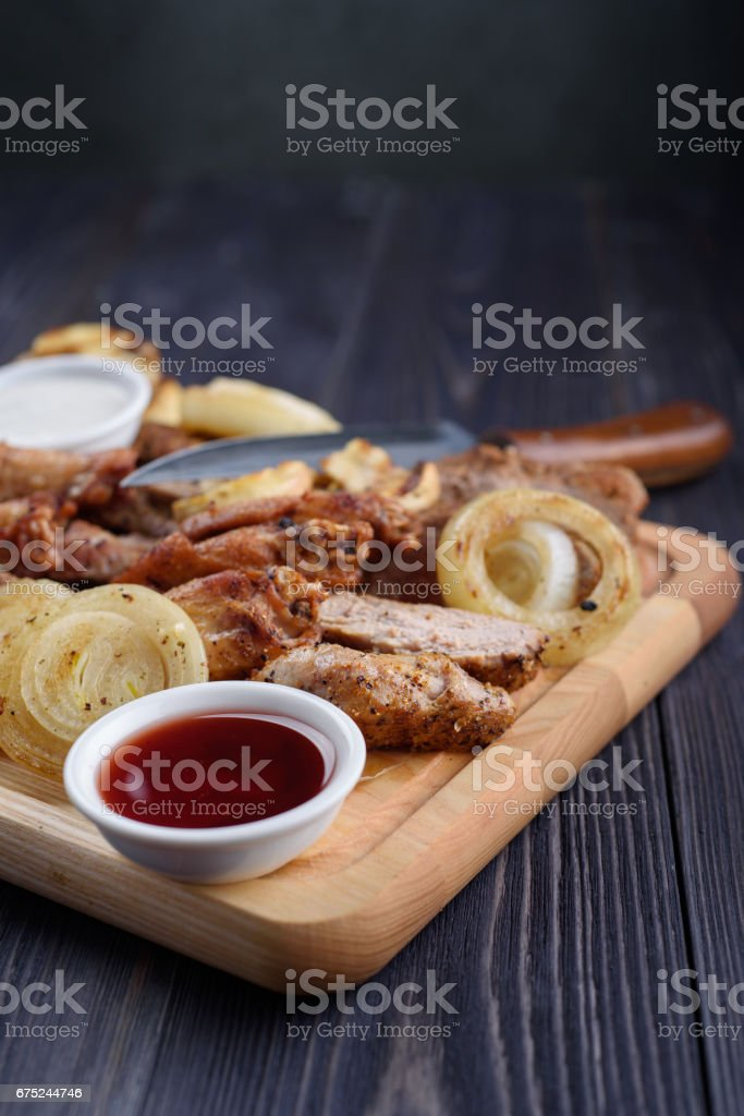 Fried meat slices of chicken wings, ham, fillets with sauce on a wooden board stock photo