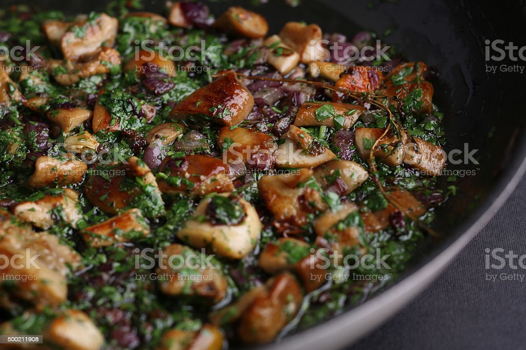 Fried mushrooms with onions and greens in a skillet on stock photo