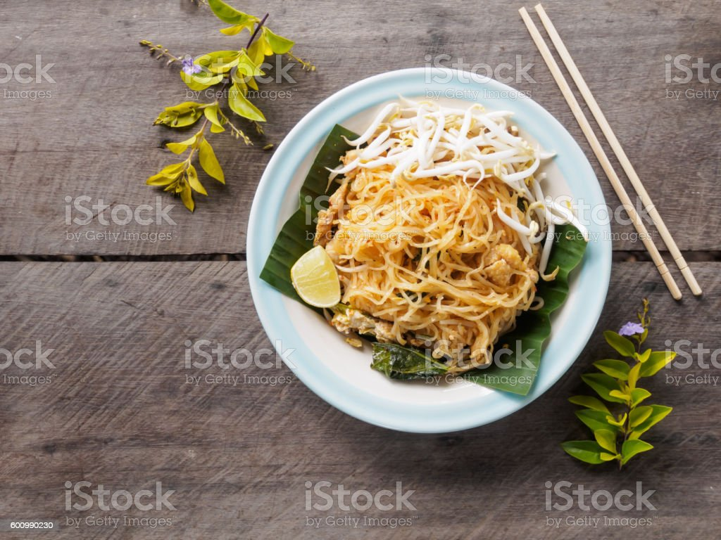 Fried noodles (Pad Thai) on wooden table, Thai food style stock photo