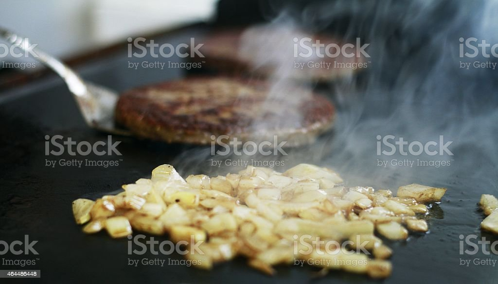 Fried onions and a beef burger on a hot plate stock photo