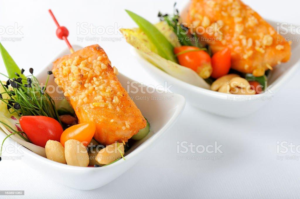 Fried Peanut Encrusted Salmon on Cucumber Salad royalty-free stock photo
