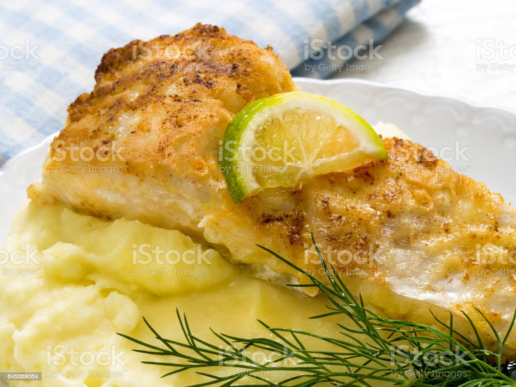 Fried perch with mashed potatoes and lime slice stock photo