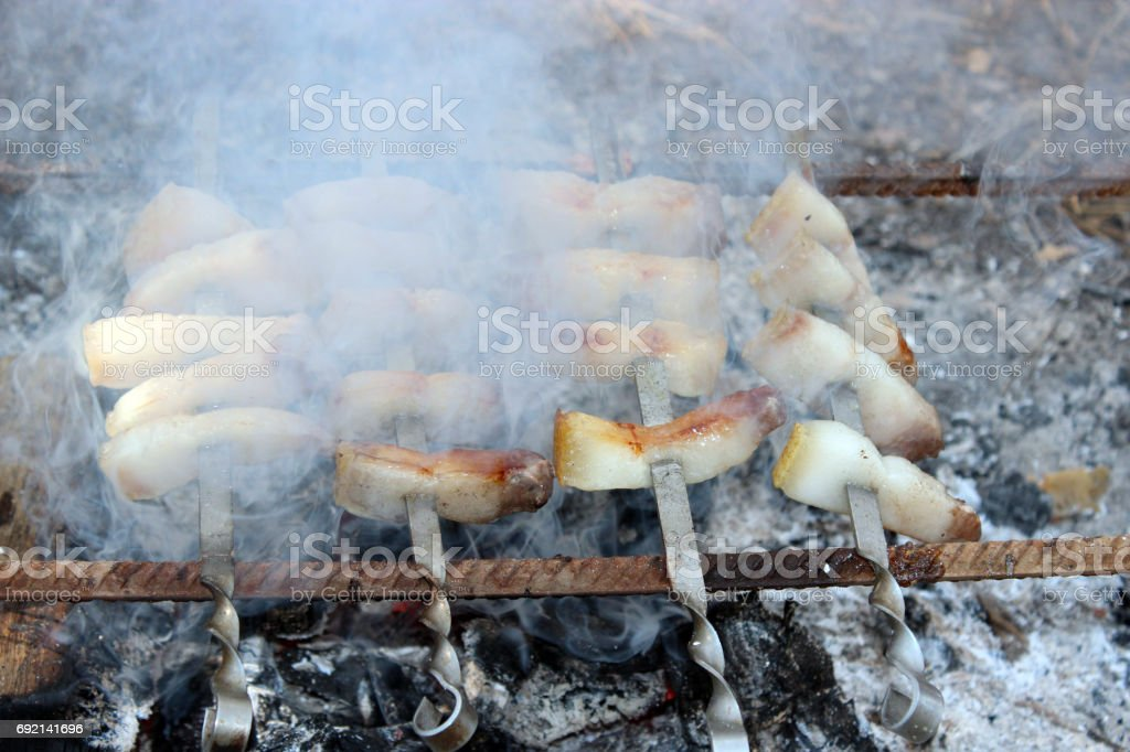 fried pieces of lard cooking on the fire stock photo