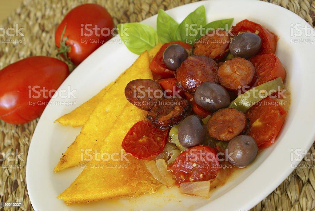 Fried polenta with tomatoes and chorizo stock photo