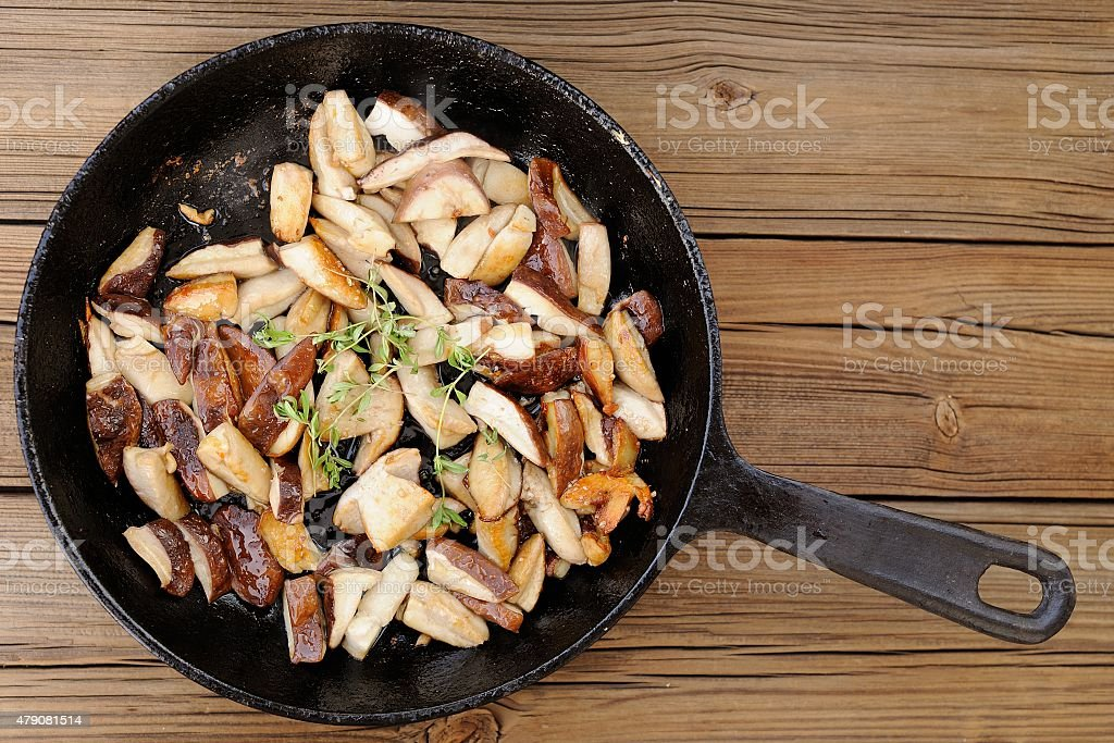 Fried porcini mushrooms with fresh thyme in cast iron skillet stock photo
