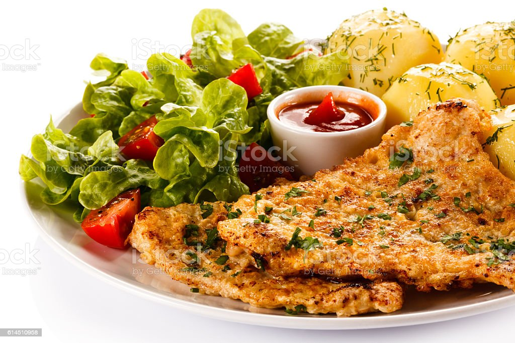 Fried pork chop, boiled potatoes and vegetable salad stock photo