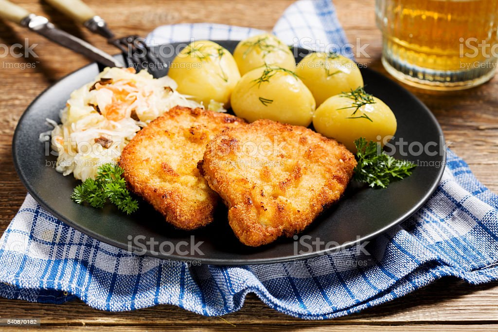 Fried pork chop in breadcrumbs, served with boiled potatoes and stock photo
