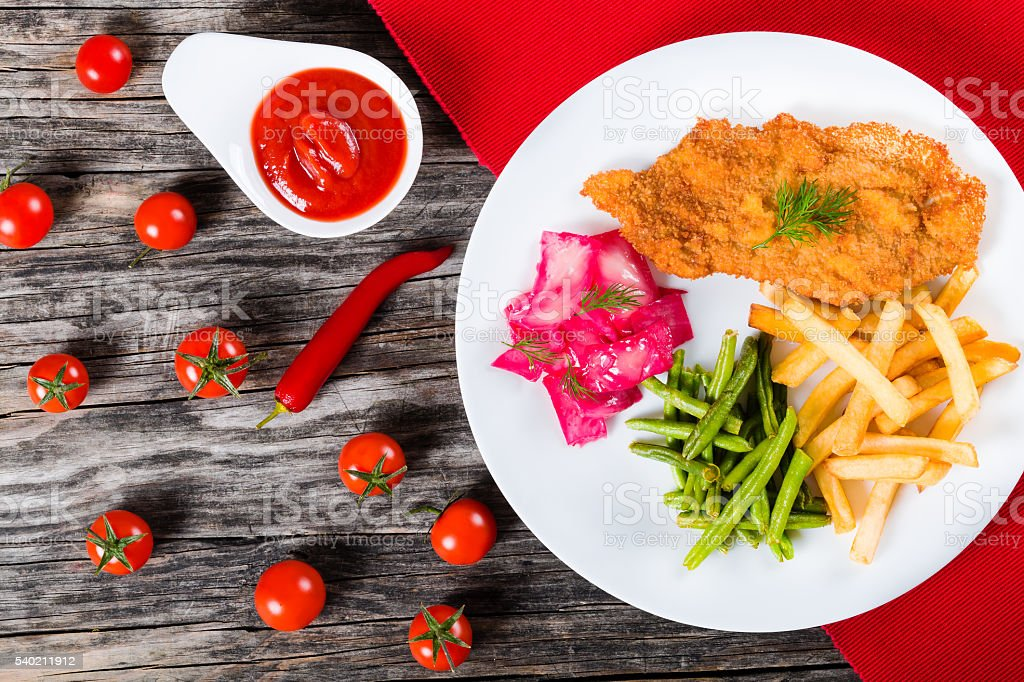 fried pork chop with french fries, green bean and salad stock photo