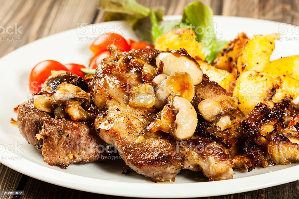 Fried pork chop with mushrooms stock photo