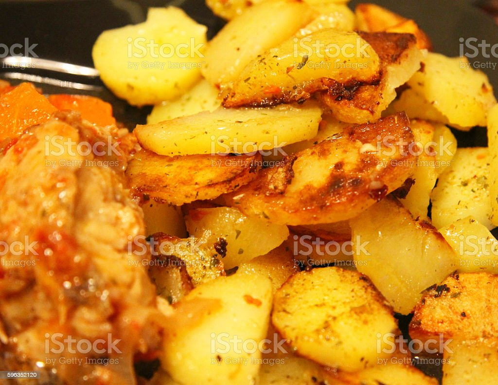 Fried potato and fried fish and the black plate stock photo