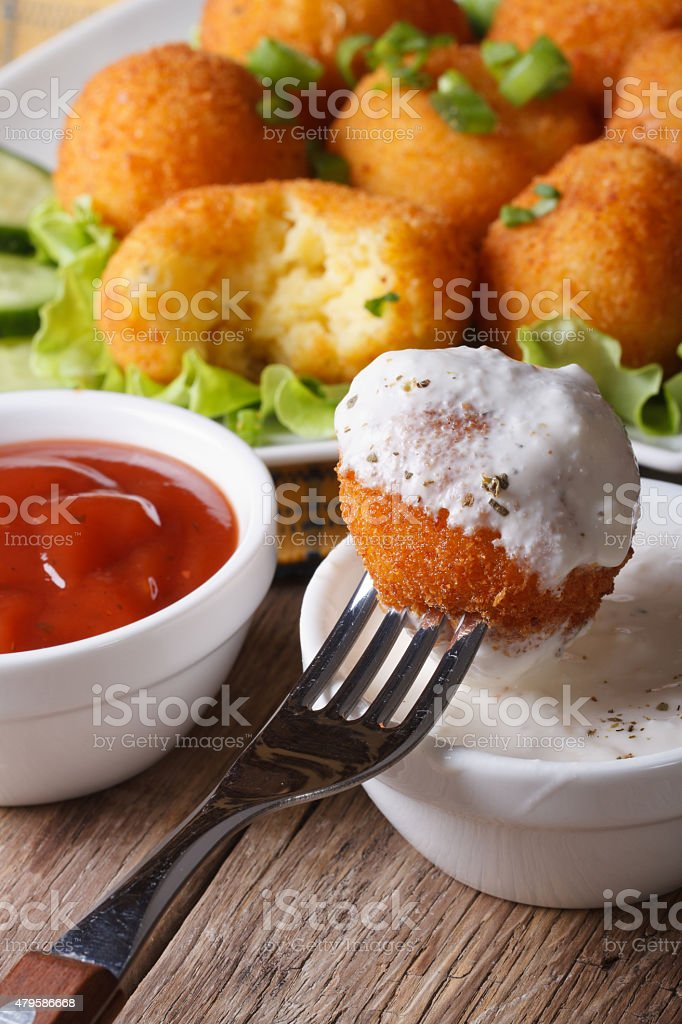 Fried potato croquettes with sour cream close-up vertical. stock photo