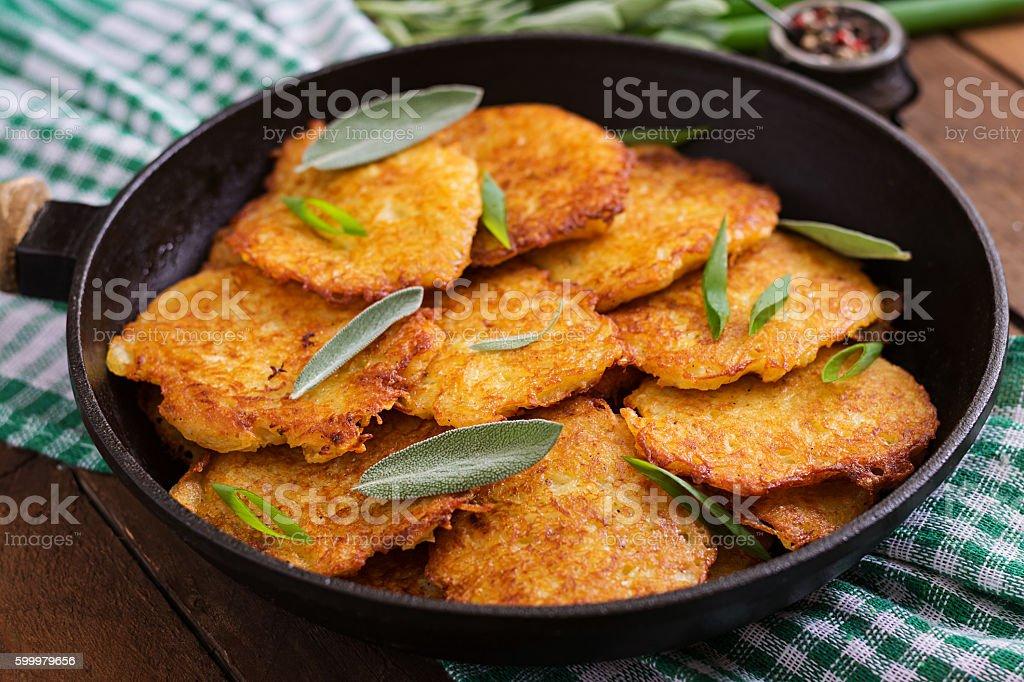 Fried potato pancakes in a frying pan stock photo