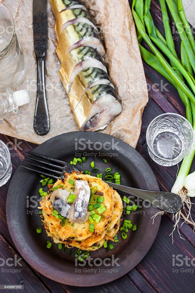 Fried potato pancakes with herring on a dark background stock photo