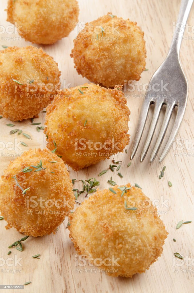 fried potato pops on wood with fork stock photo