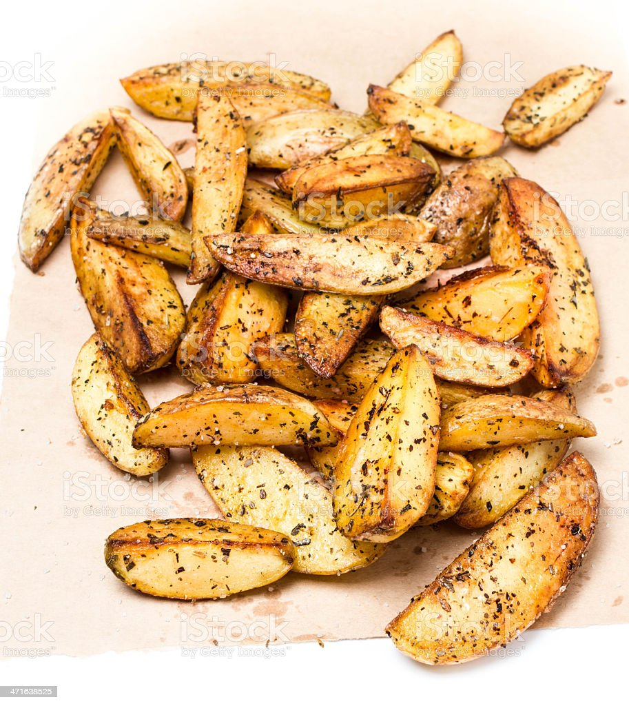 Fried potato wedges country styled  on  kraft paper. Fast food. royalty-free stock photo