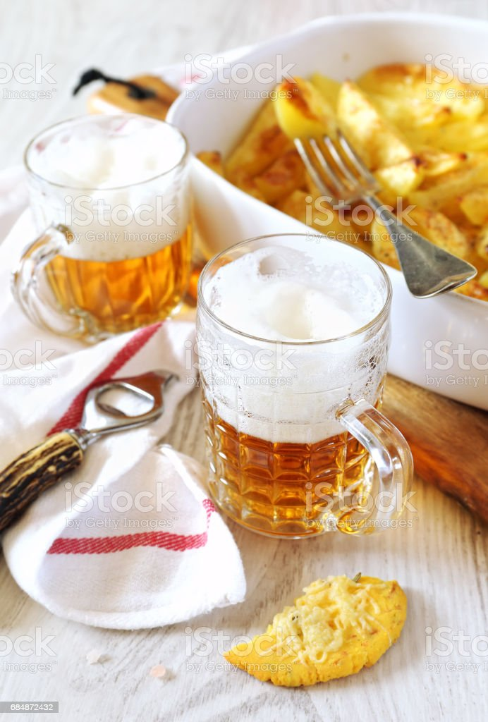 Fried potatoes and two mugs of beer stock photo