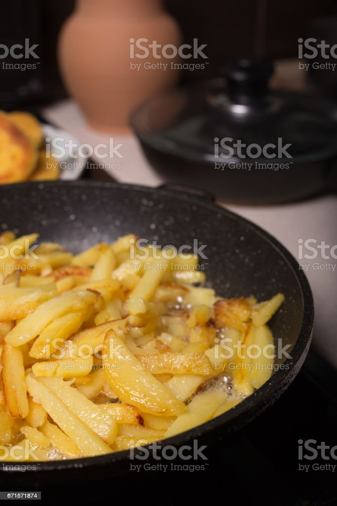 Fried potatoes in a pan stock photo