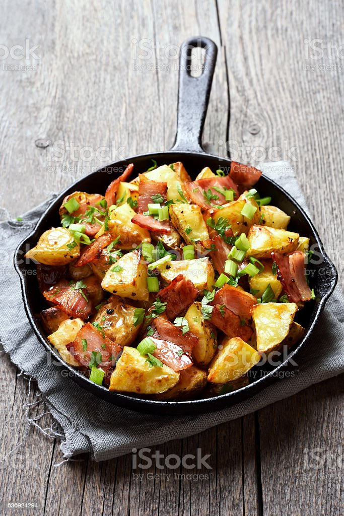 Fried potatoes with bacon and green onion stock photo