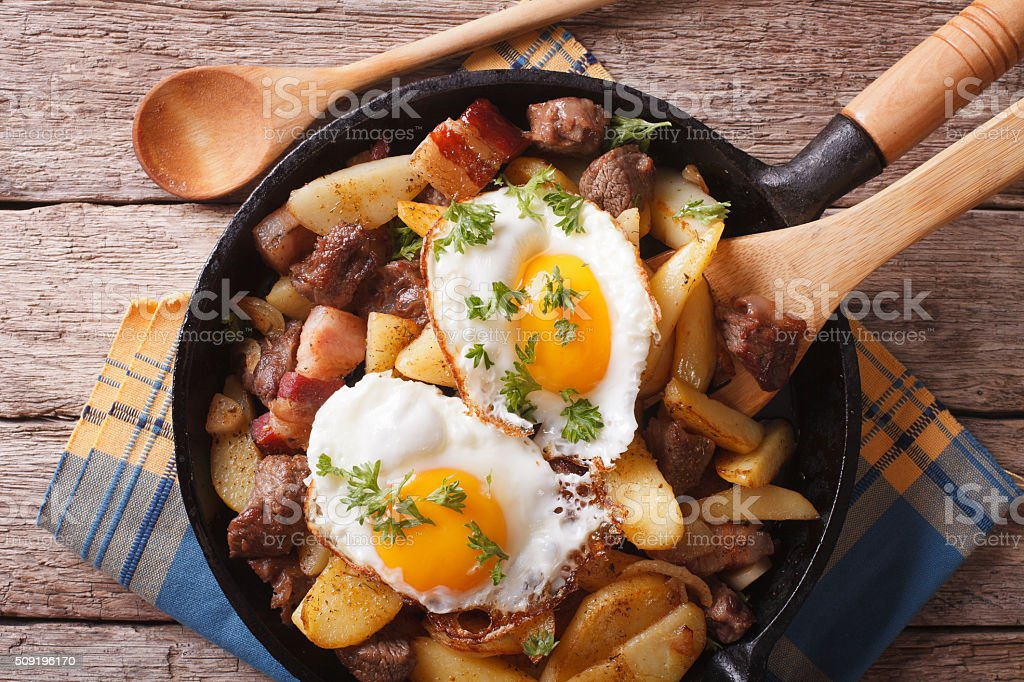 fried potatoes with meat and eggs in pan closeup. horizontal stock photo