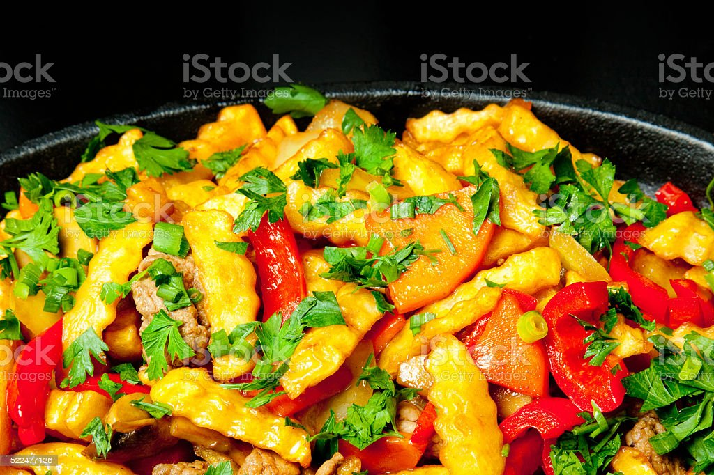 Fried potatoes with meat and vegetables in pan, junk food stock photo