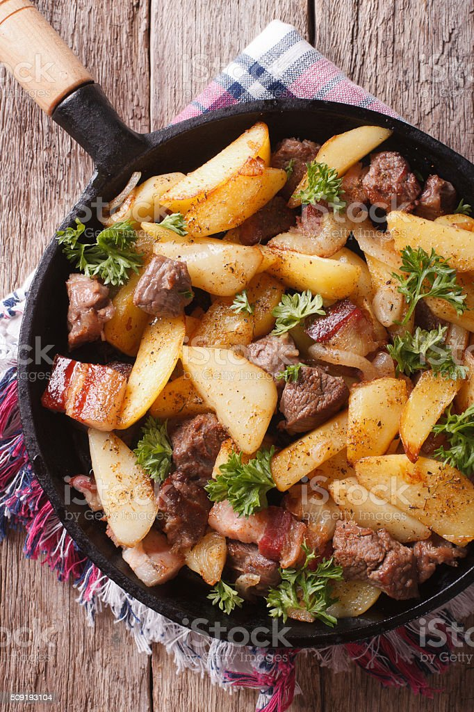 fried potatoes with meat in pan closeup vertical top view stock photo