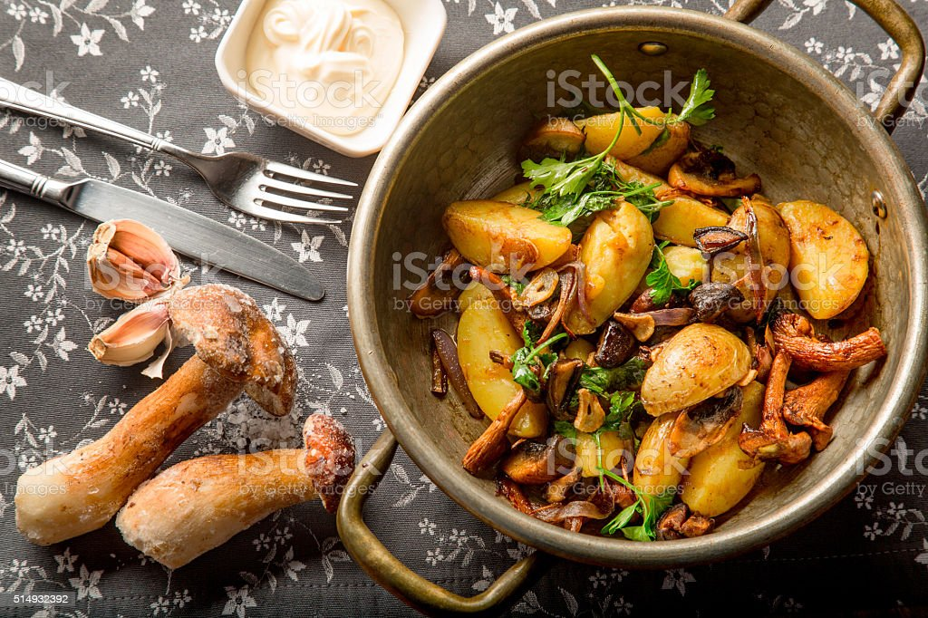 Fried potatoes with mushrooms and onions in a frying pan stock photo
