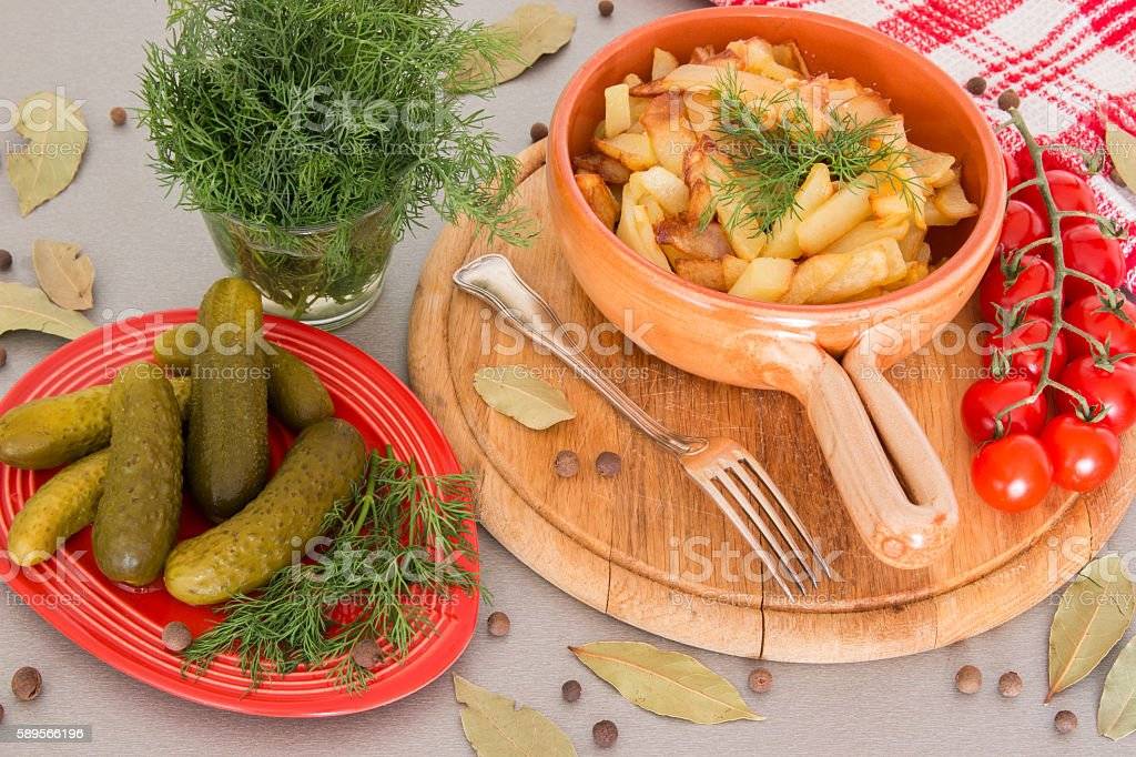 Fried potatoes with pickled cucumbers stock photo